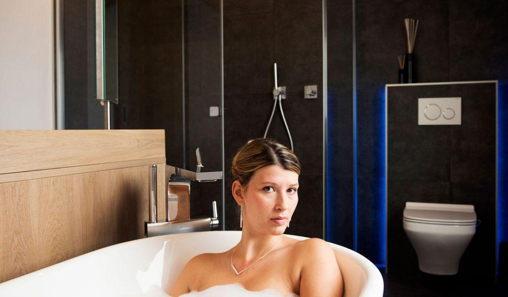 Project Renoconcept: Innovatieve meerwaarde. Foto dame in bad met volledige badkamer.